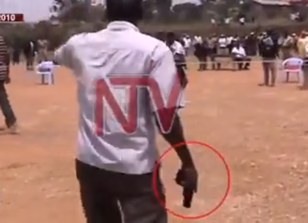 A caption from a video footage in which Ssekikubo's guard was seen wielding a pistol that was reportedly used in the shooting of one of Kutesa's men.