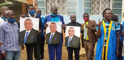 Lord Mayor Erias Lukwago's supporters holding his photos as he joins FDC at Najjanankumbi