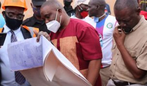 Kampla Lord Mayor M Erias Lukwago (C), peruses the site plan at the scene.